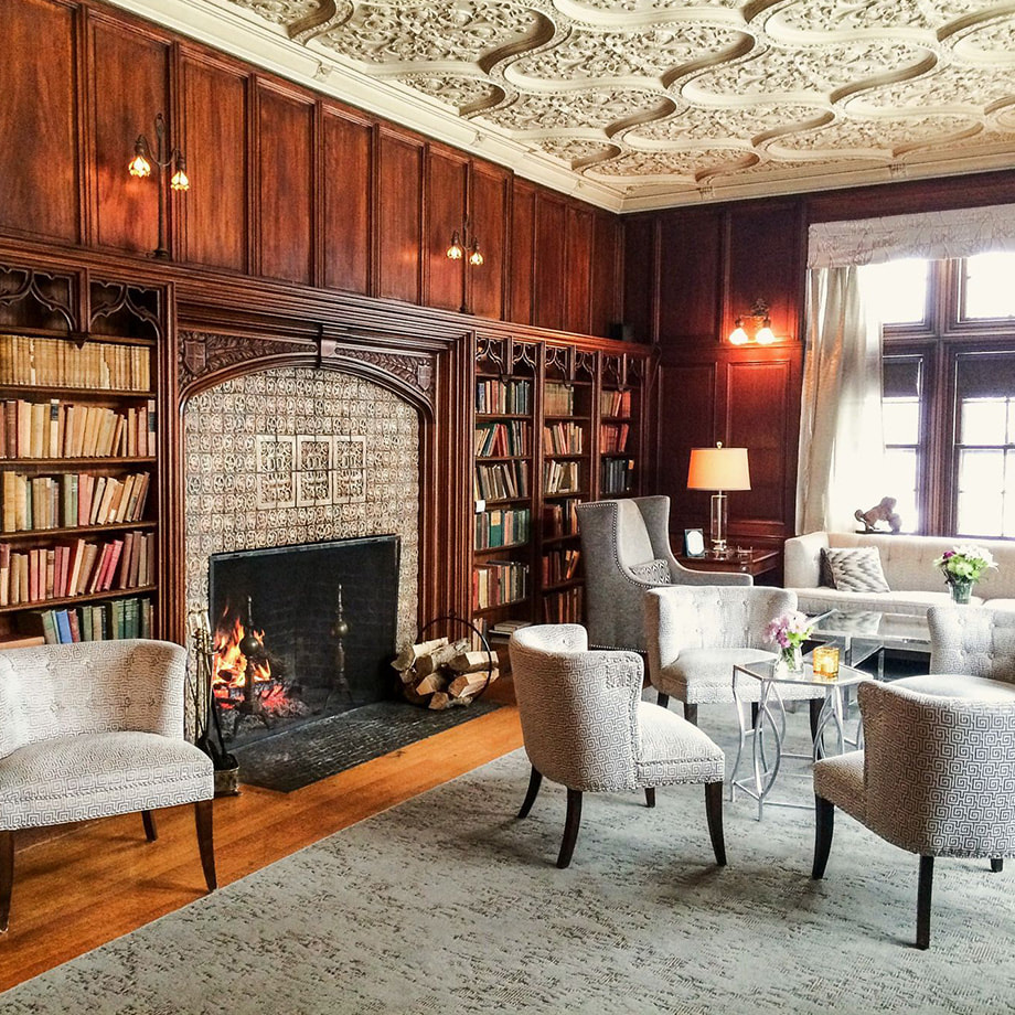 The Castle's Library featuring a large fireplace, reading chairs, and large bookshelves