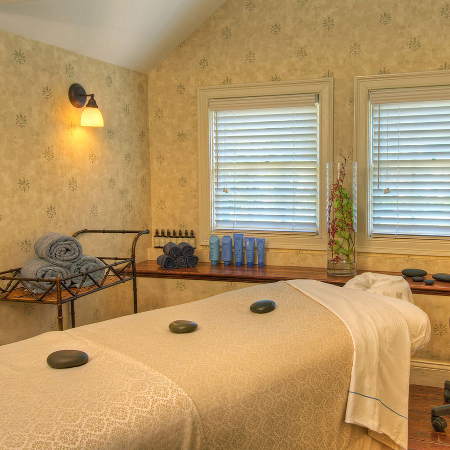 The inside of a spa room with a massage table, hot stones, and towels surrounding the table